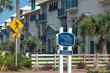Peach colored condos in Florida with a pedestrian sign out front